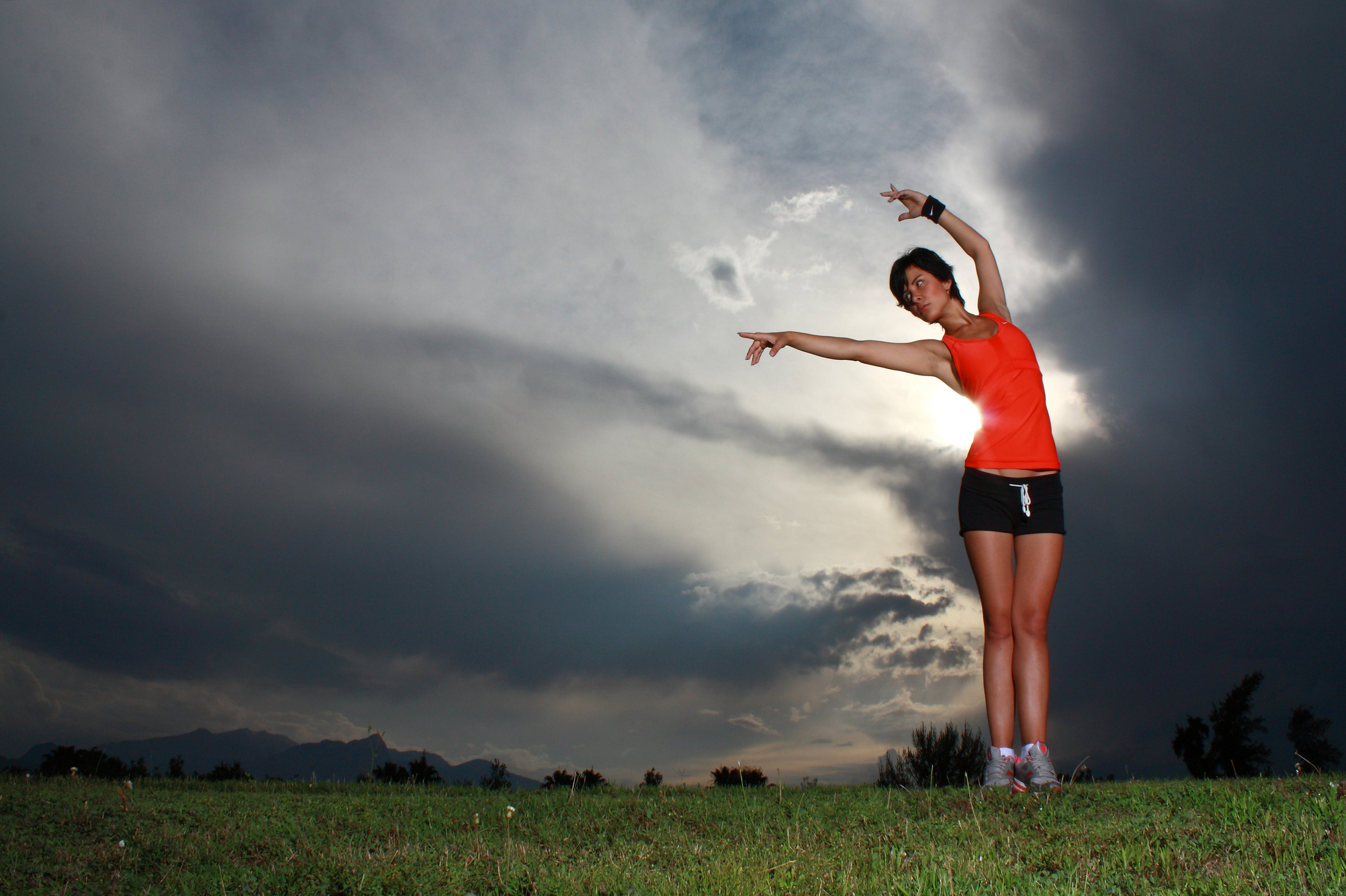 Woman Flexing Arms on Grassy Land