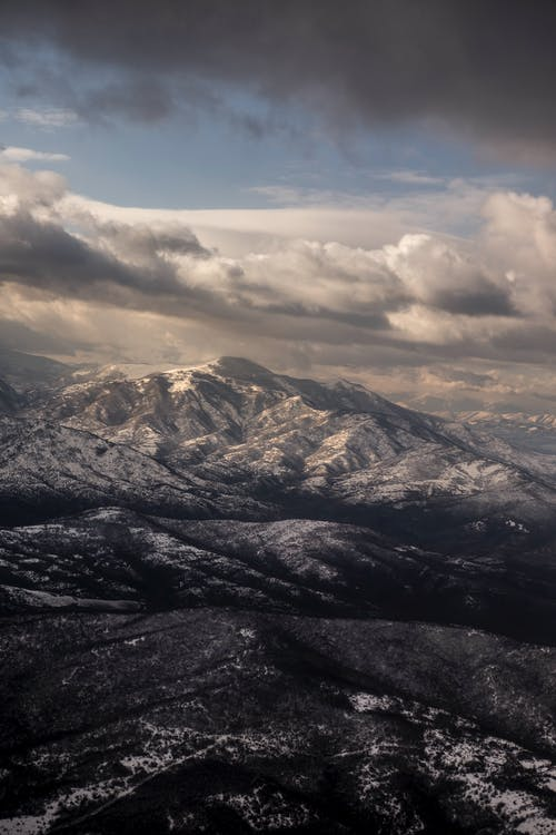 Rough snowy mountains under cloudy sky at night