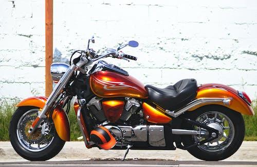 Modern motorbike on pavement near shabby wall