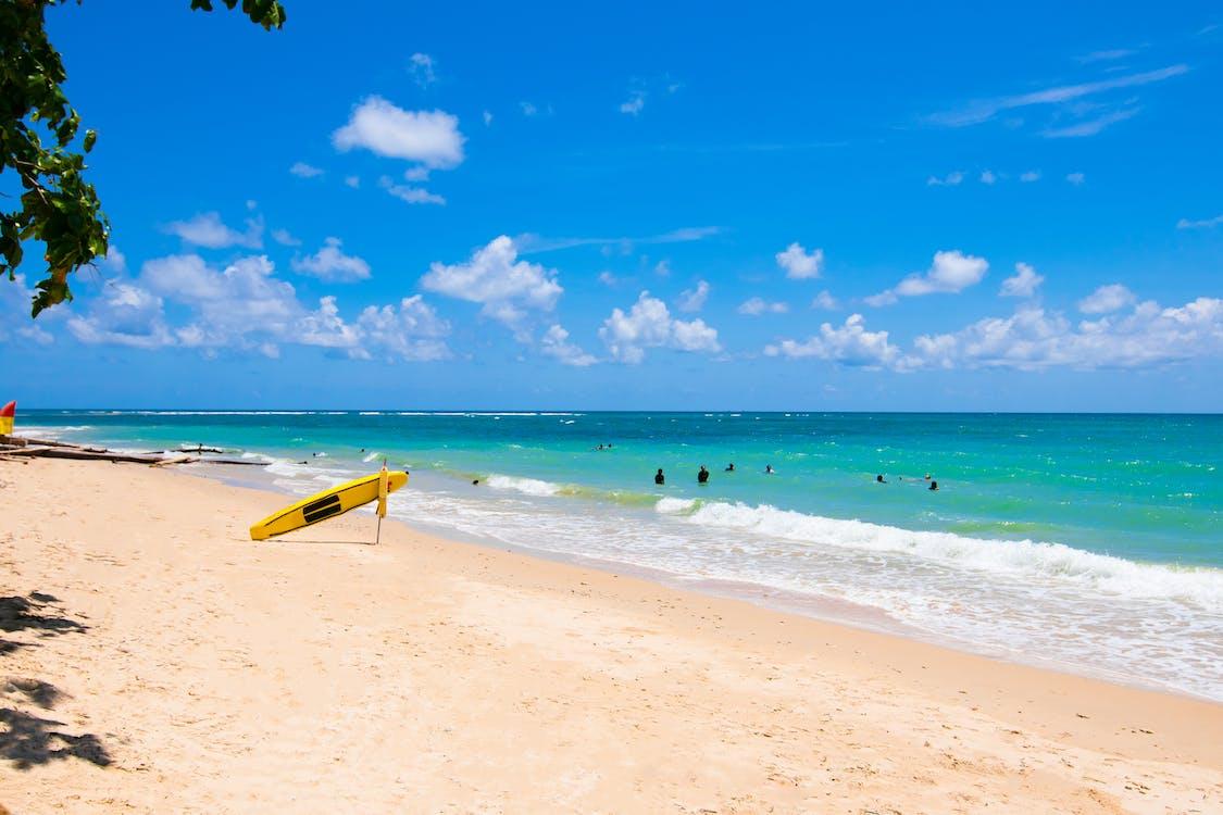 Yellow Surfboard on Beach Shore Under Clear Blue Sky