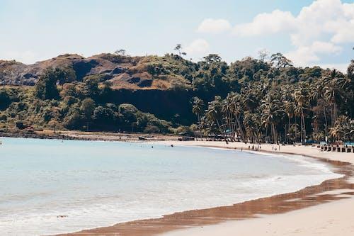 Sea water washing sandy beach in sunny day
