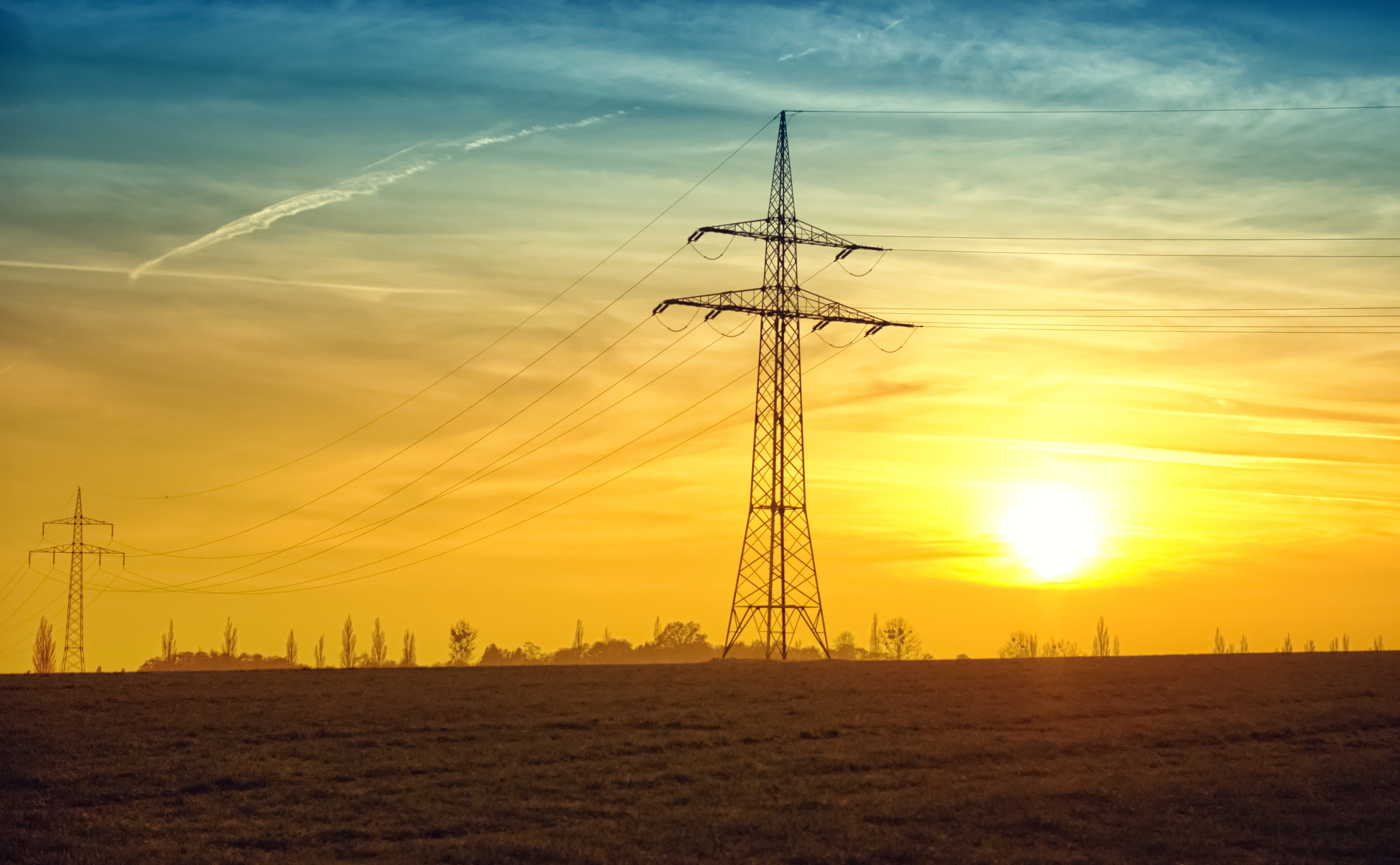 Brown Transmission Towers on Field during Sunset Landscape Photography