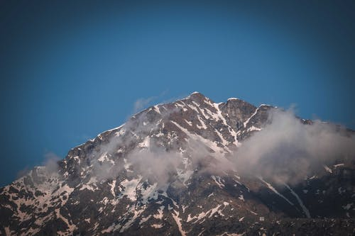 Severe scenery of rough rocky mountain with slopes covered with snow under cloudless blue sky