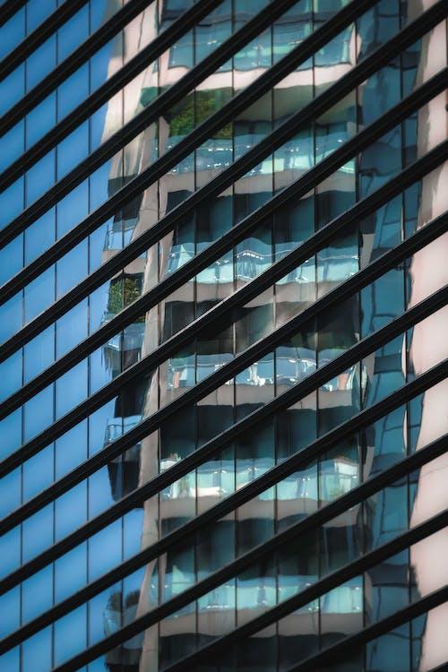 Modern glass building wall reflecting urban skyscraper