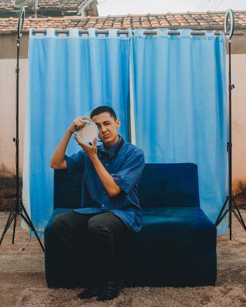 Man in Black T-shirt Sitting on Blue Sofa Chair