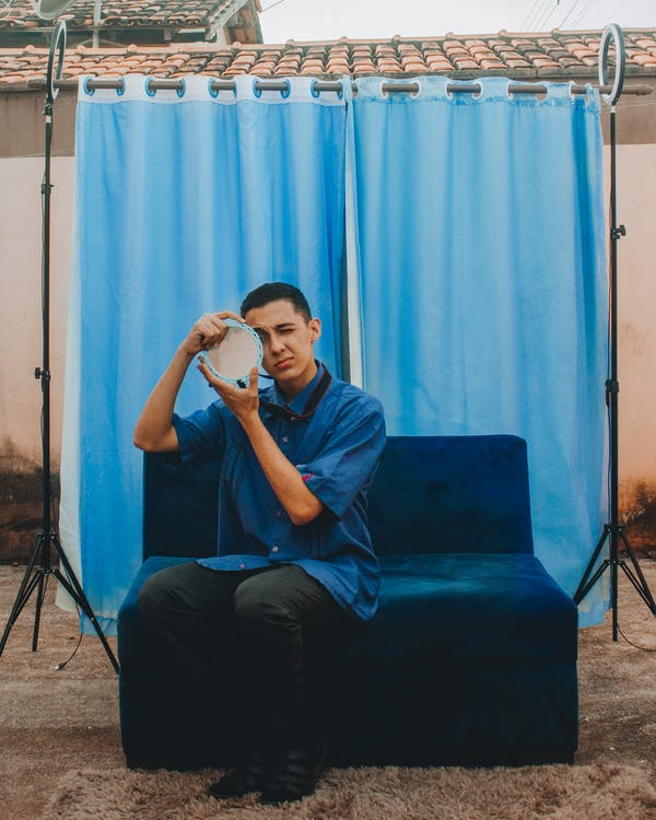 Man in Black T-shirt Sitting on Blue Sofa Chair
