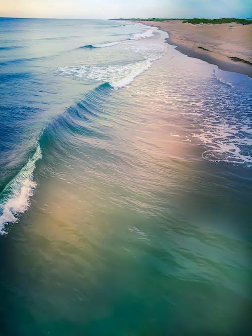 Azure waving sea washing sandy beach