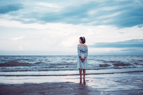 Woman in White Dress Standing on Beach