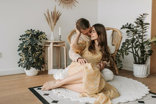 Woman in Beige Dress Sitting on White and Brown Floral Area Rug
