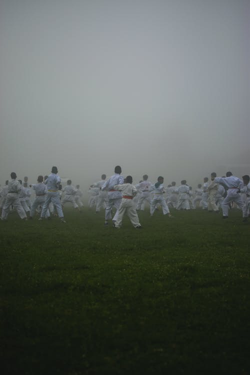 Group of People in White Uniform Standing on Green Grass Field