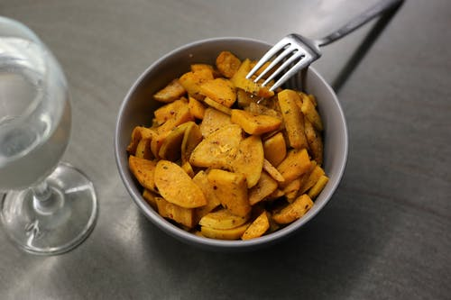 Homemade fried batata served in bowl with fork