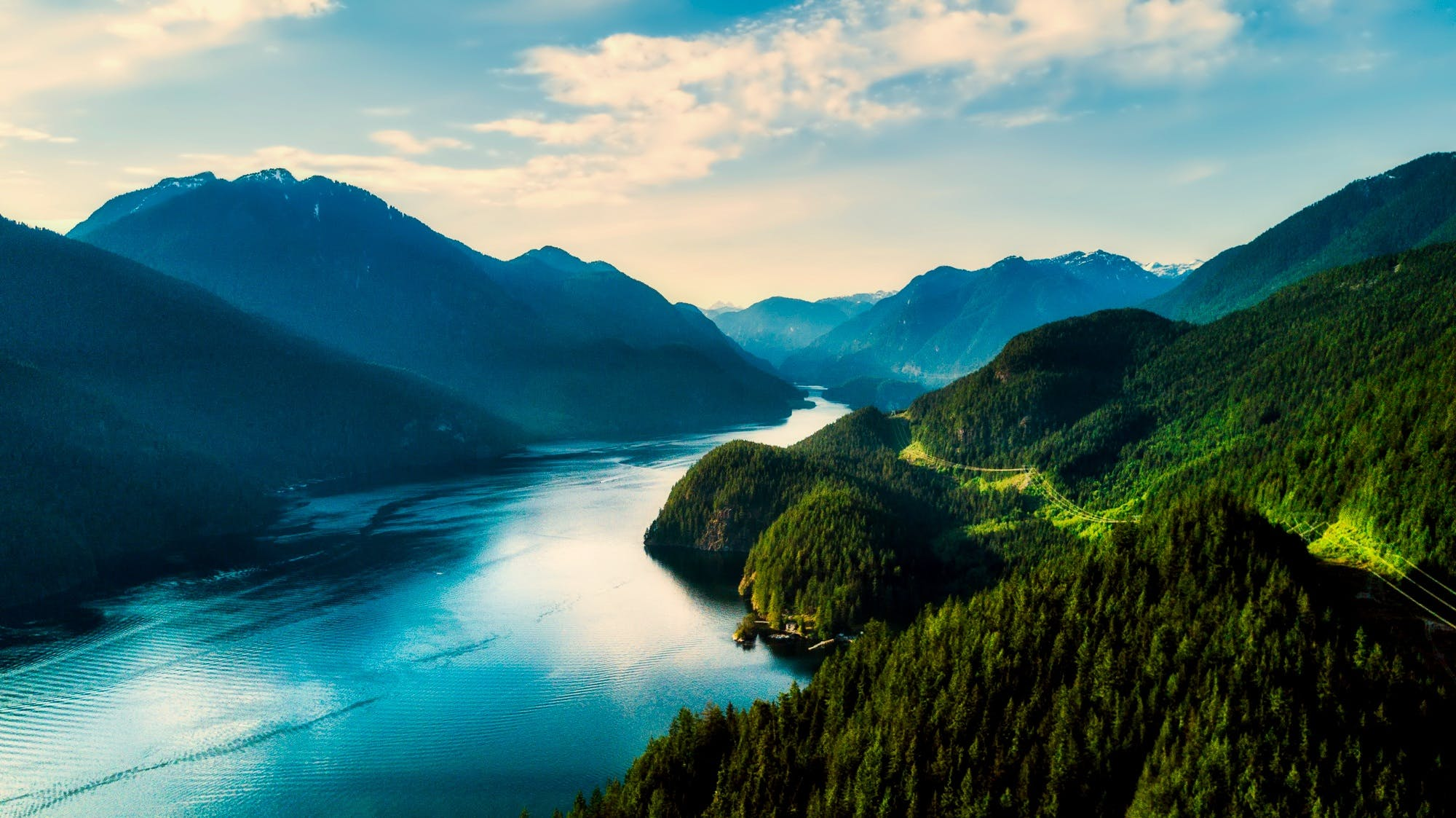Mountains With River on Center Under Blue Sky