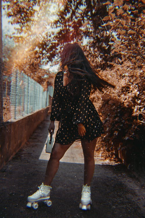 Full body of unrecognizable young female with long hair in dress roller skating on asphalt path among autumn trees