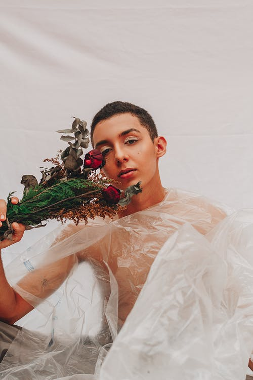Androgynous man with bouquet of flowers