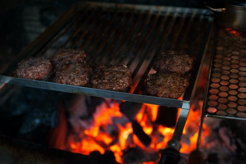 From above of appetizing meat patties grilling on metal barbecue grade above fire in kitchen