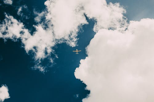 Airplane flying in cloudy blue sky