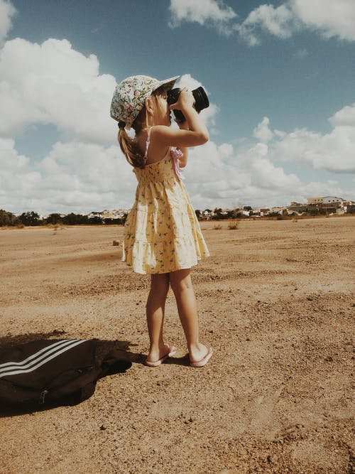 Cute little girl photographing nature on sandy beach
