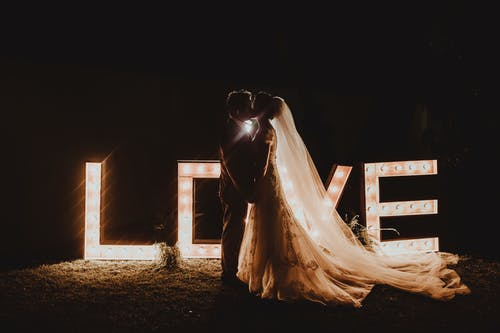Side view of unrecognizable romantic groom and bride in wedding dress and veil holding hands and kissing while standing in garden near glowing love light bulb letter