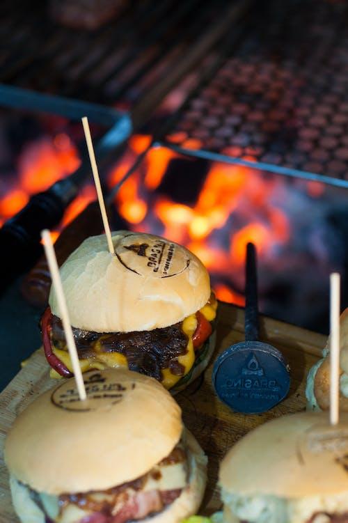 Delicious hamburgers in crispy buns near barbecue fire