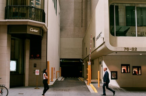 Anonymous people walking on street near contemporary buildings