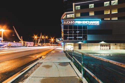 Contemporary building on illuminated city street near port at night