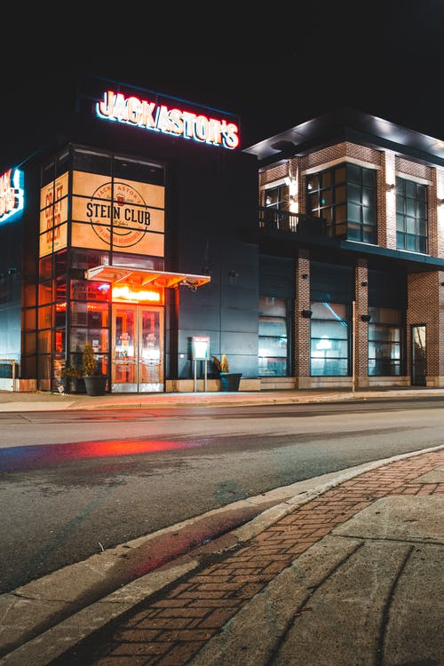 Low angle of stylish contemporary building with glowing signboard and lamps located near asphalt road in modern city at night