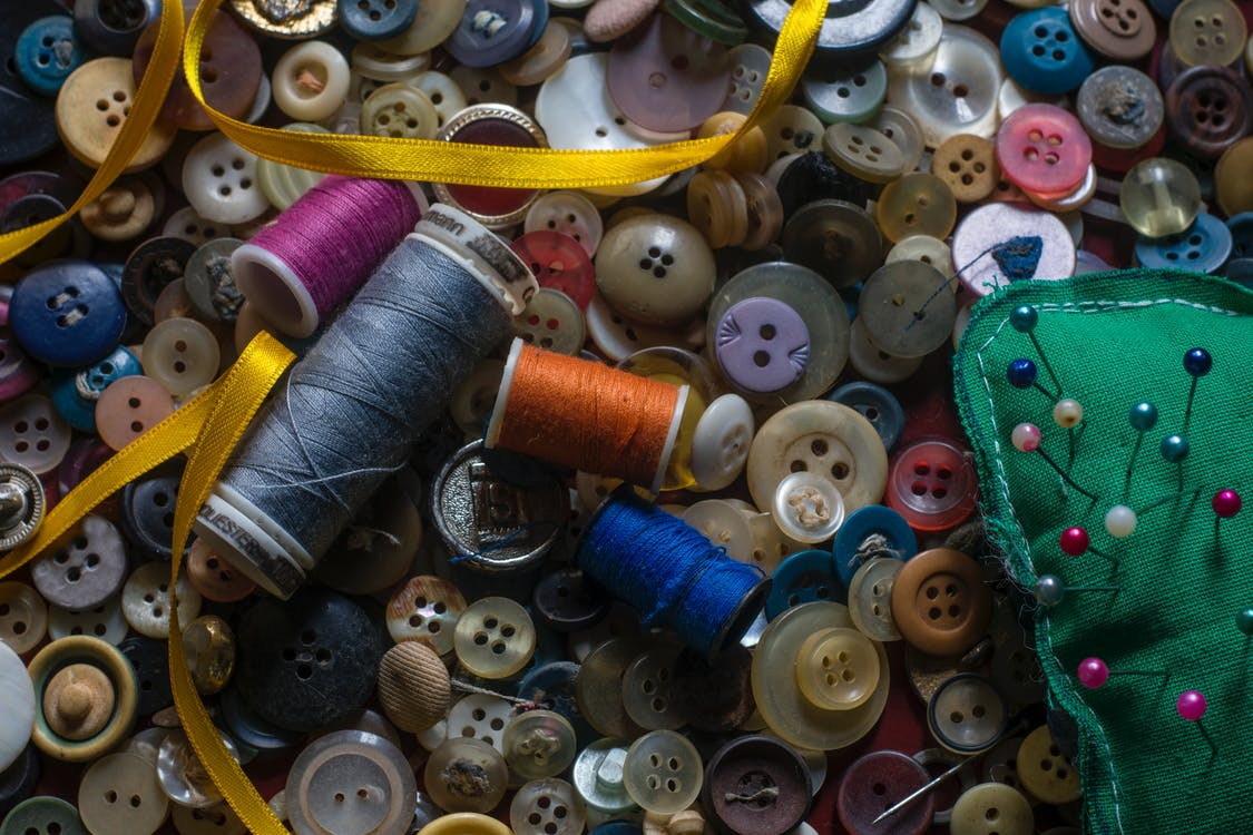 Overhead of coils of thread and round multi colored buttons composing with glossy narrow yellow ribbon and needles in pin cushion