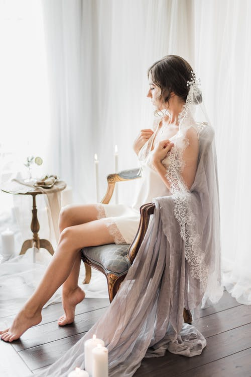 Woman in White Floral Lace Dress Sitting on Brown Wooden Chair