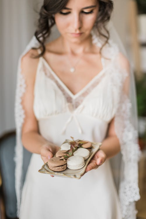Woman in White Lace Dress Holding White Ceramic Bowl With Pies