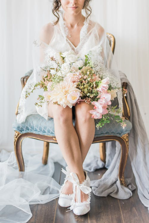 Woman in White Floral Dress Holding A Bouquet Of Flowers