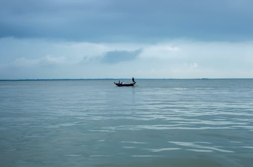 Distant people floating on boat with paddles on rippling water against cloudy sky and horizon line in nature on summer day