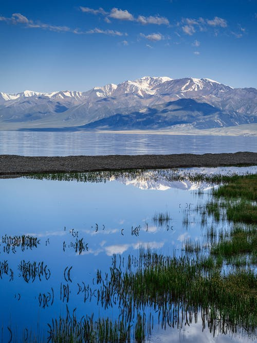 Sand bar surrounded by reservoir and grass next to mountain range with snow on top under vibrant blue sky covered with clouds