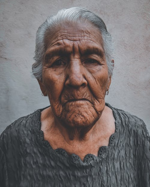 Unemotional senior ethnic female in casual clothing with wrinkled face looking at camera