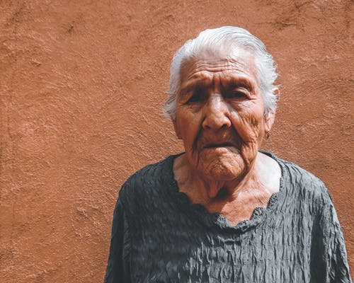 Old woman near beige wall in sunlight