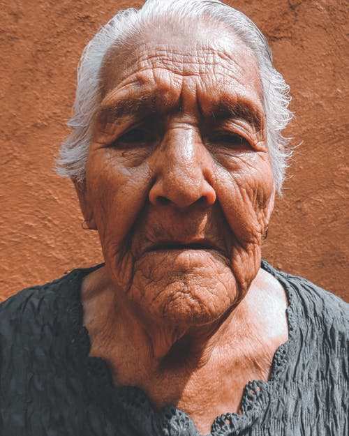 Pensive old ethnic female with wrinkled face and silver hair looking at camera with mouth opened