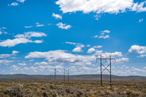 Gray Metal Electric Posts on Brown Grass Field Under Blue and White Cloudy Sky
