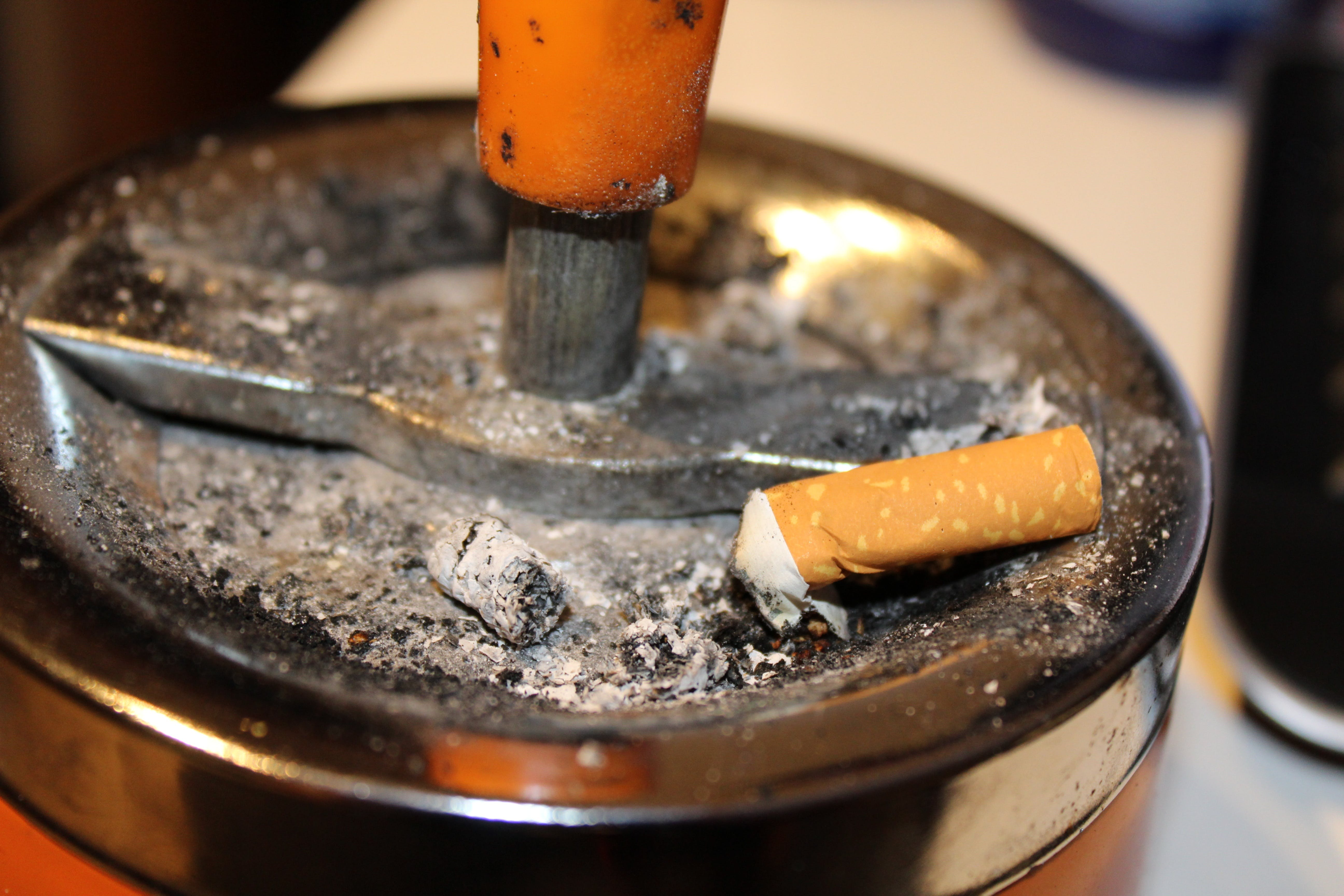 Gray Ashtray Filled With Cigarette Butt