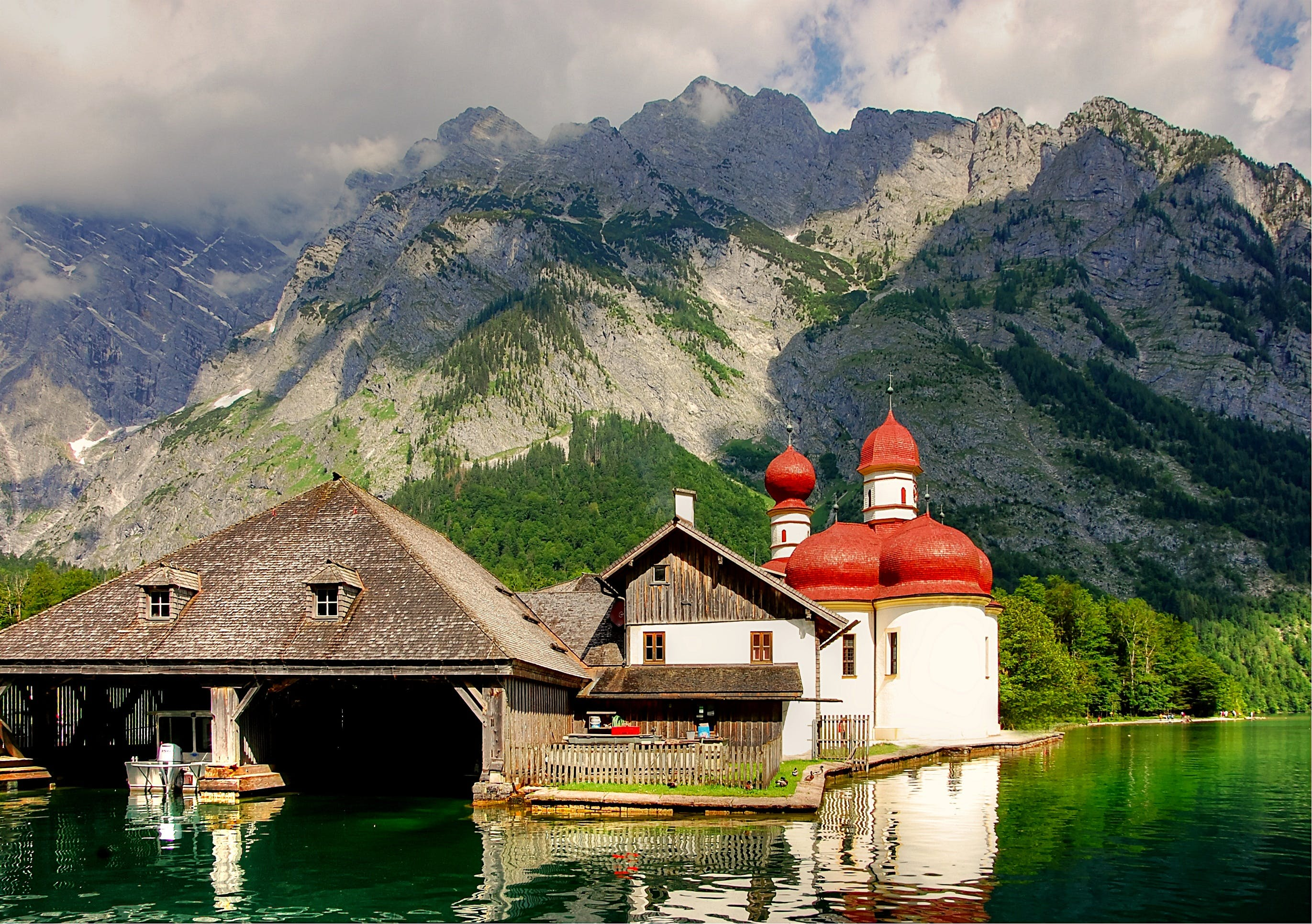 White, Red, and Brown House Beside Body Water Near Mountain