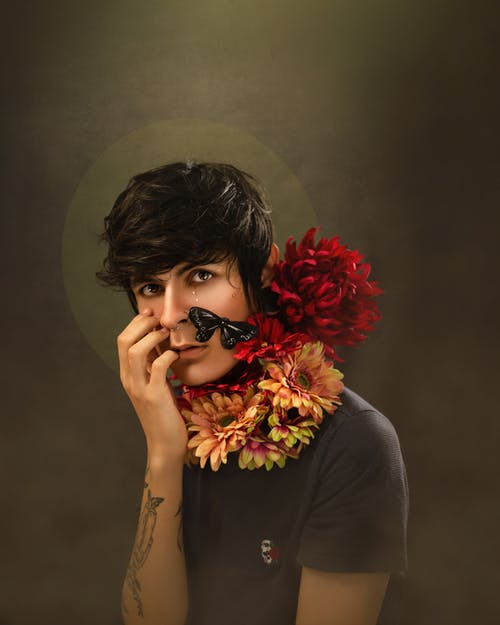 Stylish young man with flowers around neck