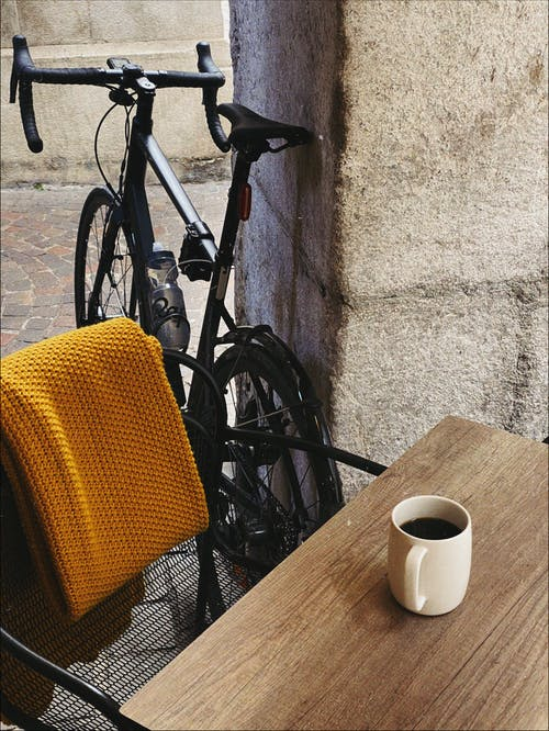 Black Bicycle Beside White Ceramic Mug on Brown Wooden Table