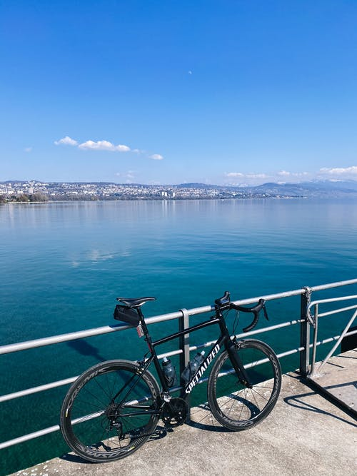Black Bicycle Leaning on Railings Near Body of Water
