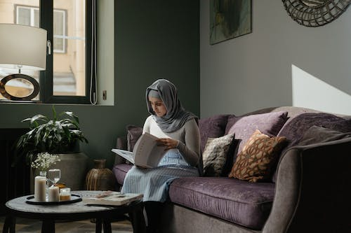 Woman Reading Book Sitting on Couch