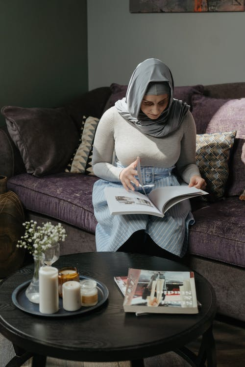 Woman in White Hijab Sitting on Couch Reading Newspaper