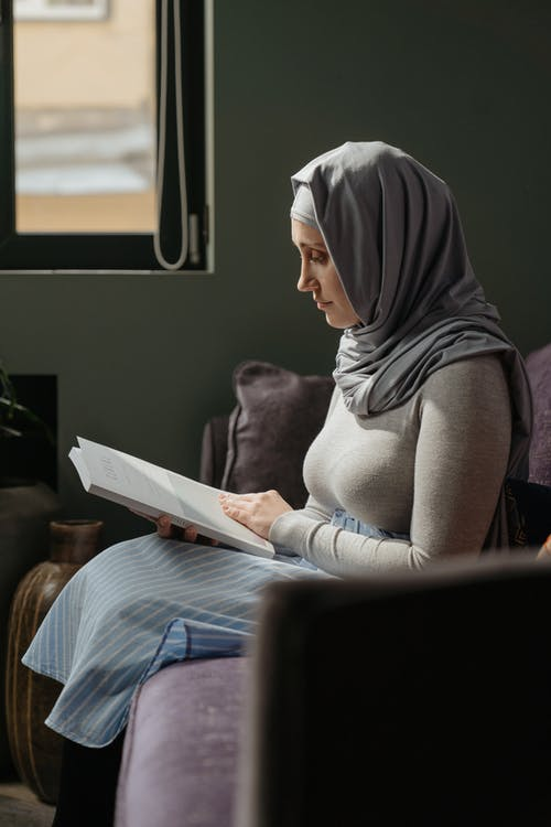 Woman in Gray Hijab Sitting on Chair Reading Book