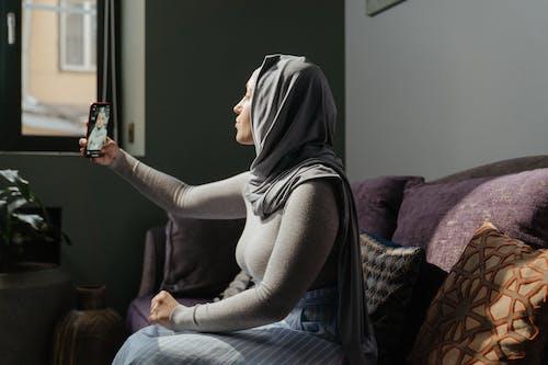 Woman in Gray Hijab Sitting on Purple Sofa