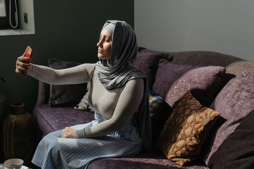 Woman in Gray Hijab Sitting on Purple Couch