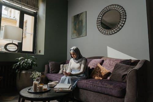 Woman in White Hijab Sitting on Brown Sofa