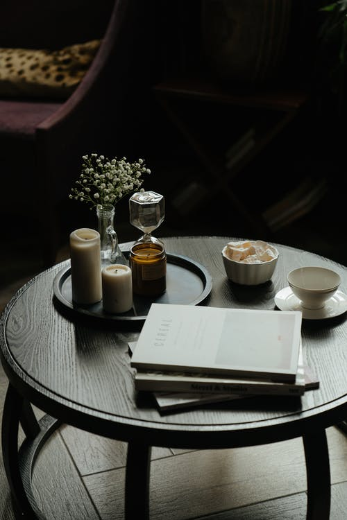 White Ceramic Cup on White Ceramic Saucer Beside White Book on Brown Wooden Table