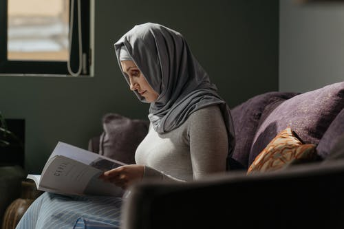 Woman in Gray Hijab Reading Book