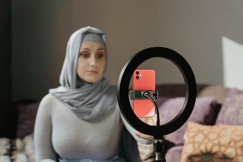 Woman in Gray Hijab Holding Magnifying Glass
